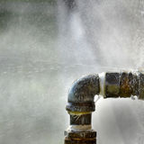 Old Leaky Pipes. Old rusty pipe with leak and water spraying out Stock Image