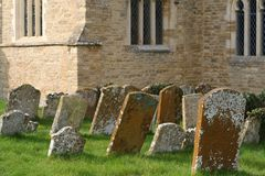 Old leaning gravestones in a churchyard. Royalty Free Stock Image