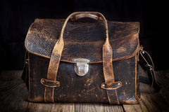 Old leather bag on wooden background. Vintage style Stock Photos