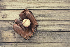 Old leather baseball mitt and ball on grunge wood background Royalty Free Stock Photo