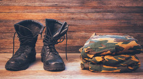 Old leather black men boots and military uniform on a wooden background front view Stock Photos