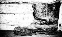 Old leather boot. Side view of one old wrinkled and weathered black ankle boot sitting on a wood board shelf in black and white Stock Photography
