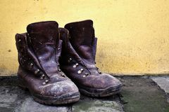 Old leather shoes on brick groundwork and yellow wall in background royalty free stock photo