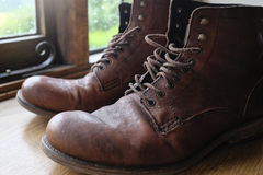 Old leather boots. A pair of old brown leather boots on a windowsill Royalty Free Stock Photos