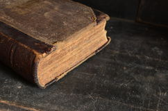 Old leather bound book laying on a dusty wooden bookshelf Royalty Free Stock Photos