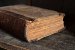 Old leather bound book laying on a dusty wooden bookshelf. Old leather bound book laying on a dusty old wooden bookshelf royalty free stock photography