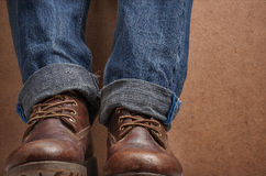 Old leather brown boots and blue jeans Royalty Free Stock Photos