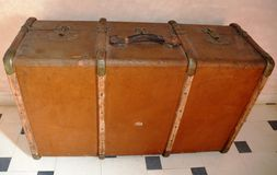 Old Leather Brown Suitcase on mosaic tile. Immigration was and will remain stock image