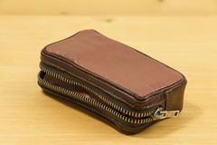 Old leather case. Old, fashion styled leather case on a wooden desk Royalty Free Stock Photos