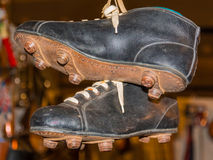 Old leather hanged soccer boots. Close up of Vintage leather hanged black football shoes Stock Images