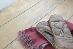 Old leather mittens and scarf on wood table Royalty Free Stock Photography