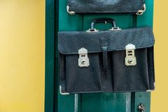 Old leather school bag hanging against green wooden door. Background royalty free stock photo