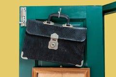 Old leather school bag hanging against green wooden door. Background stock image