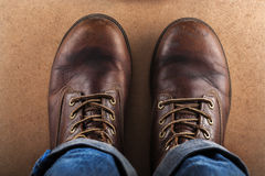 Old leather shoes and blue jeans photographed from above Royalty Free Stock Images