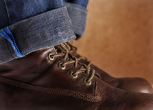 Old leather shoes brown color with blue jeans. Royalty Free Stock Images