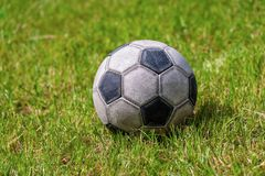 Old leather soccer ball on grass Football Sport. Close-up of an old leather soccer ball on green grass, football sport concept stock photos