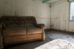 Old leather sofa. In an abandoned house Stock Photos
