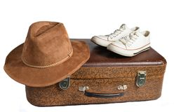 Old leather suitcase, retro sneakers, felt hat isolated on white background. The concept of travel royalty free stock photography