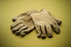 Old leather work gloves 2. Old tattered leather work gloves on a gold background Royalty Free Stock Images