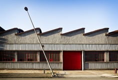 Old left factory. Old factory with red carpentry in and some of its broken crystals. A lamppost, inclined by the blow of some vehicle, increases the sensation of Royalty Free Stock Photos