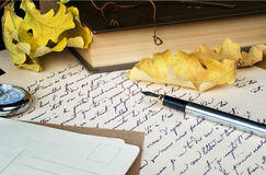 Old letter, pen, book and yellow leaves Royalty Free Stock Images
