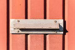 Old letterbox or mailbox in the gate door traditional way of delivering letters or mail to the house address close up.  Stock Image