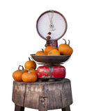 Old libra balance and pumpkins. Isolated on white. Libra old with over pumpkins. An old balance has on his plate and side numerous pumpkins. Object isolated on Royalty Free Stock Photography