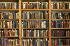 An Old Library with Hardcover Books on Pine Shelves. Very old hardcover books with worn bindings on pine shelves in the Whalers Church in Grytviken South Georgia Royalty Free Stock Photos