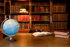 Old library interior. An open book on a desk beside a blue world globe with bookshelves behind in a beautiful old library Stock Photography