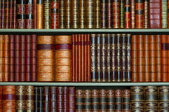 Old library of vintage hard cover books on shelves