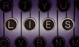 Old Lies. Close up of old typewriter keyboard with scratched chrome keys that spell out LIES. Lighting and focus are centered on LIES Royalty Free Stock Photo