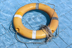 Old life buoy on the blue water of the pool. Royalty Free Stock Images