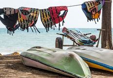 Old life jacket is hanging near the kayak boat. Royalty Free Stock Photos