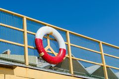 Old lifebuoy attached to the railing on the rescue post royalty free stock photo