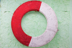 Old lifebuoy on a wall. Old lifebuoy hanging on a green wall Stock Image