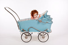 Old light-blue doll-venture with a doll. Old light-blue doll-venture in which an old doll sits Stock Photography
