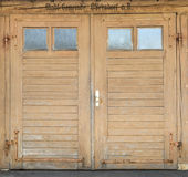 Old light brown garage door with windows Royalty Free Stock Image
