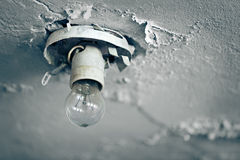 Old light bulb on ceiling of abandoned house Stock Images