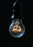 Old light bulb glowing in dark Stock Image
