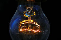 Old light bulb glowing in dark.  Stock Images