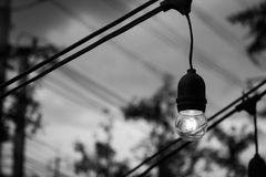 Old light bulb glowing in the dark. Black and white image. Stock Photography