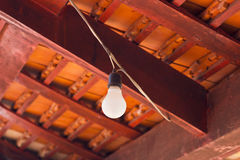 Old light bulb under the roof. Old light bulb under the red roof Royalty Free Stock Photo