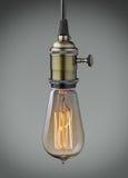 Old light bulb. Vintage hanging light bulb over gray background Royalty Free Stock Image