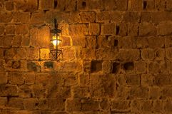 Old light lamp at night hanging on a medieval street fortress wall. Background royalty free stock photography