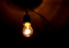 Old light shines dimly in the basement of an old Stock Photography