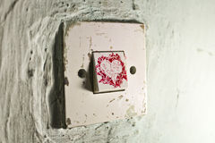 Old light switch with red paint heart on old cracked green wall Royalty Free Stock Photo