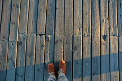 Old Light wooden board with well visible structure of wood and with standing on her legs male orange bootscovered with frost Royalty Free Stock Images