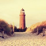 Old lighthouse above dunes and pine tree  before sunset. Tower illuminated with strong warning light. Lighthouse built from red bricks, gallery with iron Royalty Free Stock Photos