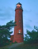 Old lighthouse above dunes and pine tree  before sunset. Tower illuminated with strong warning light. Lighthouse built from red bricks, gallery with iron Stock Photos