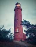 Old lighthouse above dunes and pine tree  before sunset. Tower illuminated with strong warning light. Lighthouse built from red bricks, gallery with iron Stock Image